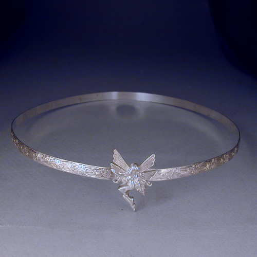 A fairy is set on this 1/3 inch sterling silver floral patterned band.